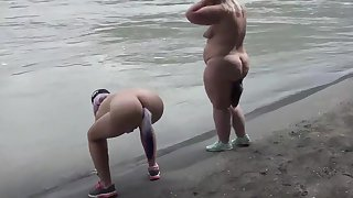 Lesbians nudists walk along the river bank with anal plugs inside a big asses. Fetish.